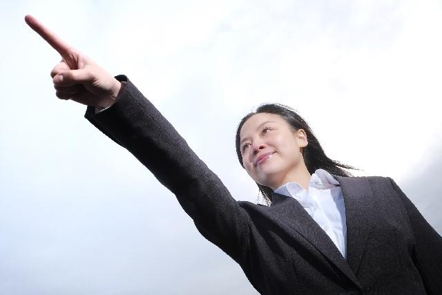 女の人が指さしている写真
